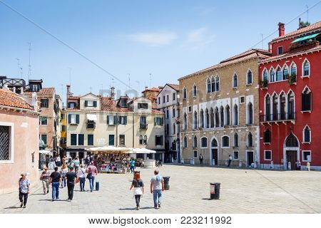 VENICE, ITALY - May 18, 2017 : Tourists foot Street in Venice. its entirety is listed as a World Heritage Site, along with its lagoon. VENICE, ITALY.
