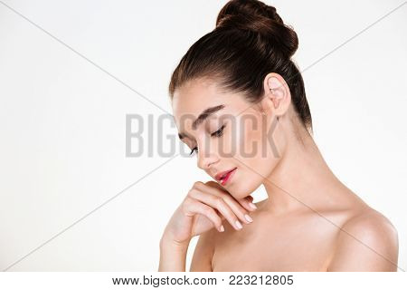 Horizontal portrait of tender woman being half-naked posing over white background, with face downward