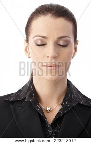 Closeup portrait of businesswoman concentrating with eyes closed.