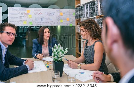 Businesswoman talking in a business meeting to teamwork sitting at table in company headquarters