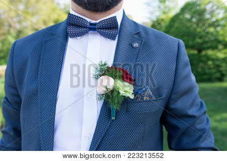 Boutonniere on the suit jacket of the groom. Stylish groom in blue jacket, white shirt and blue necktie with boutonniere. Wedding