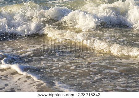Coastal wave rolls to shore, white foam, strong wind and storm at sea