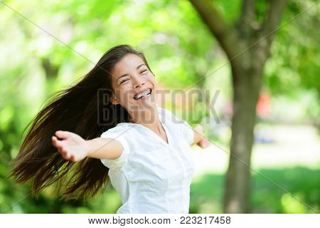 Cheerful young woman with arms outstretched enjoying in park. Portrait of beautiful female is in casuals. Joyful woman is enjoying nature during summer.