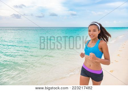 Running woman. Fitness runner jogging during outdoor cardio workout on beach. Beautiful fit mixed race sport model outdoors wearing sportswear sports bra and activewear shorts.