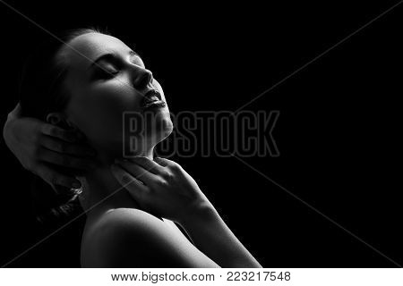 sensual aroused woman with closed eyes on black background, monochrome