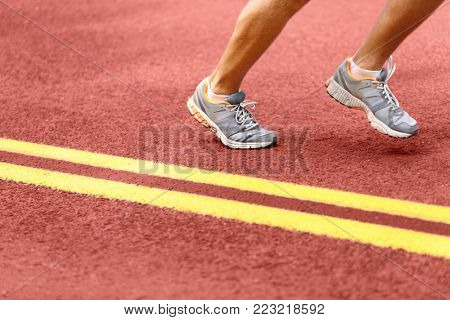 Man running on road. Low section of sporty male wearing sports shoes. Athletic runner is exercising by double yellow lines.