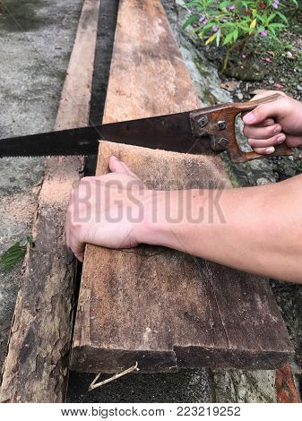 Man cutting an old plank with hand saw.
