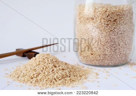 Pink Rice In A Glass Jar With A Lid Yoke, Brown Wooden Sticks, White Background