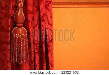 red curtain with magnificent pom-pom on an orange colored background, close-up