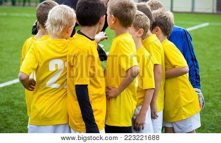 Young football soccer players with coach. Coach motivate children. Kids soccer united team. Youth sports team with football coach. Pep talk with coach before the final match. Soccer school tournament