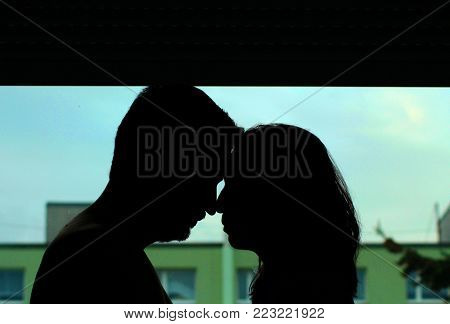 Silhouettes of a young couple in front of a window in a dwelling.