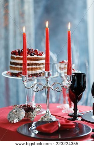 Delicious sweet buffet with berry cake. Sweet holiday buffet with cake and glasses with champagne. Candy Bar for Valentins day with candles.