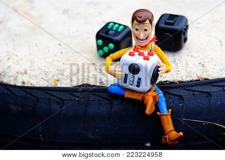 Songkhla, Thailand - July 3, 2017: Woody playing Fidget Cube stress reliever, Fingers Toy (Relax)