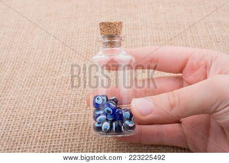 Hand holding Evil eye bead in bottle as  souvenir