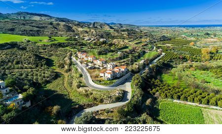 Aerial bird's eye view of Goudi village in Polis Chrysochous valley, Paphos, Cyprus. View of traditional ceramic tile roof houses, trees, hills and Akamas - Latchi beach bay from above.