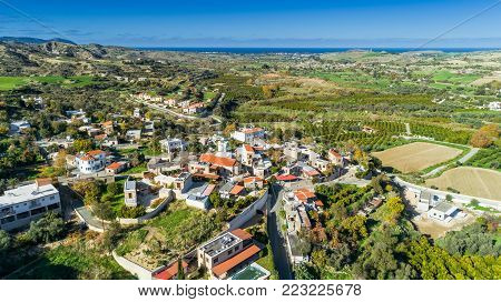 Aerial bird eye view of Goudi village in Polis Chrysochous valley, Paphos, Cyprus. View of traditional ceramic tile roof houses, church, trees, hills and Akamas - Latchi beach bay from above.