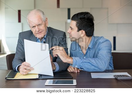 Business assistant showing papers to boss while they discussing contract. Concentrated senior businessman reading agreement and listening to manager in office. Teamwork concept