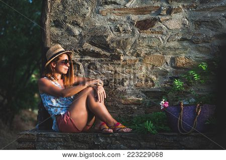 Young woman enjoying sunset at balcony at sunset