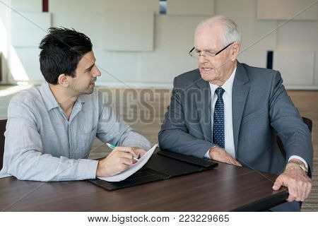 Confident manager interviewing senior businessman while holding survey. Inquisitive young male accountant working with papers and consulting with colleague in office. Insurance concept poster