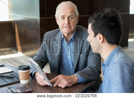 Confident senior manager setting tasks to employee and showing report on tablet during staff meeting. Concentrated handsome financial advisor working with young entrepreneur in office. Planning business concept
