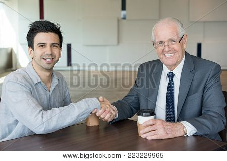 Content confident business partners shaking hands and looking at camera. Jolly excited investor and startupper concluding deal. Negotiating concept