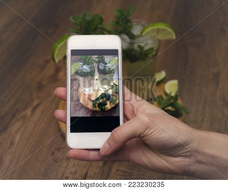 photograph a summer drink of mojito, mohito with mint, ice and lime, in glasses, on a wooden table, macro photography