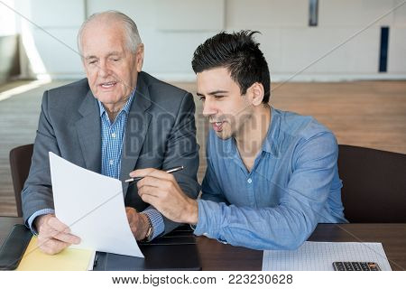 Confident young financial advisor explaining agreement to client and pointing at business paper during meeting. Cheerful young male accountant assisting manager to cope with paperwork. Agenda concept