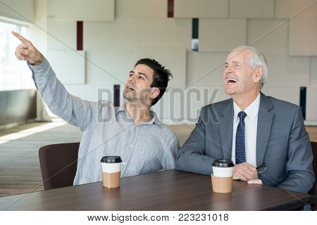 Inquisitive man pointing at projection screen showing mistake to colleague during presentation. Misunderstanding young employee talking to senior businessman at seminar. Discussion concept