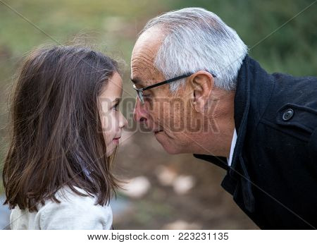 grandpa and granddaughter playing nose to nose with nose