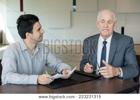 Pensive senior executive speculating on business strategy while discussing document with colleague at meeting. Introspective businessman expressing his view on new approach. Consulting concept