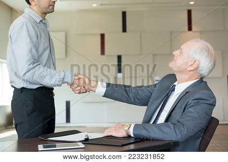 Respectable boss making handshake with new employee while hiring him. Serious confident senior executive congratulating business partner with new contract. Recruitment concept