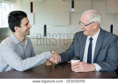 Satisfied senior executive congratulating new employee with start of collaboration. Cheerful successful man with coffee cup shaking hand of new business partner while they sitting at table. Achievement concept