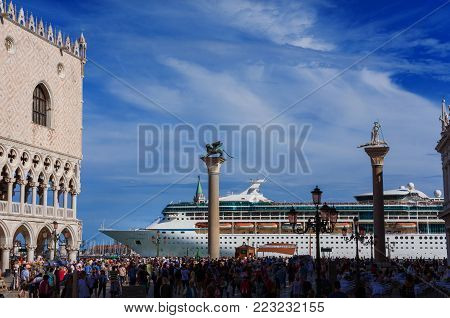 VENICE, ITALY - JUNE 18: Tourists watch giant cruise ship in front of Saint Mark Square. A very big issue for the preservation of Venice fragile enviroment and city historic heritage June 18, 2016 in Venice, Italy