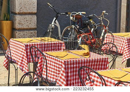 Wind curles a napkin on the table covered with a plaid tablecloth of a street cafe in Verona, Italy