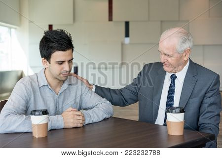 Understanding boss consoling young employee. Upset young manager disappointed with failure. Confident senior mentor supporting colleague in board room. Meeting concept
