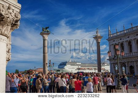 VENICE, ITALY - JUNE 18: Tourists watch giant cruise ship in front of Saint Mark Square. A very big issue for the preservation of Venice June 18, 2016 in Venice, Italyfragile enviroment and city historic heritage