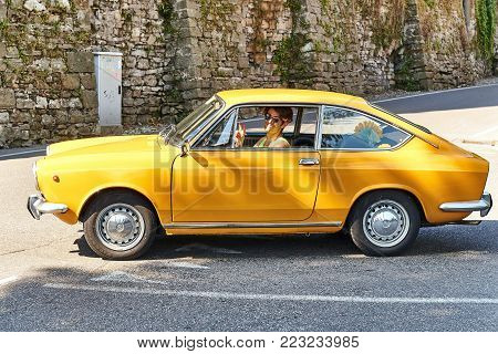 Bergamo, Italy - July 08, 2017: Young man driving yellow vintage Fiat 850 Sport Coupe released circa 1970 in Italy.