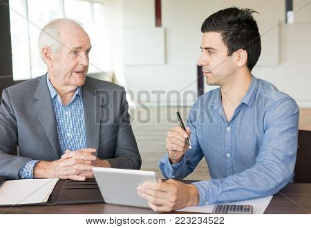 Two serious business people discussing in meeting hall. Experienced businessman consulting young professional with tablet. Business meeting and consulting concept