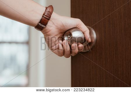 Male hand open door knob or opening the door