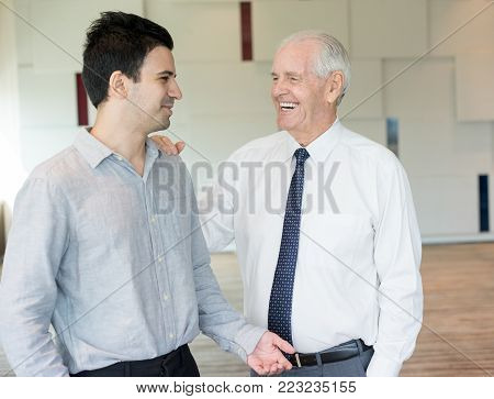Content senior man in tie slapping on shoulder young colleague. Boss encouraging manager for closing good deal. Business meeting and success concept