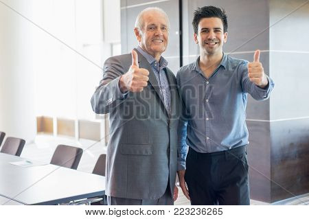 Smiling senior man in suit and his young male coworker showing thumb up at camera. Senior coach and young employee satisfied with their cooperation. Business meeting and coaching concept