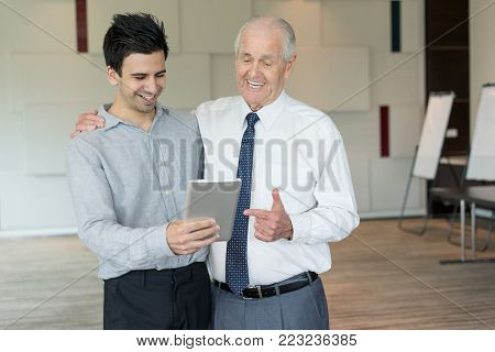 Content senior man in white shirt and tie pointing at tablet screen for junior colleague noticing. Smiling office workers having video call or conference. Business meeting and communication concept