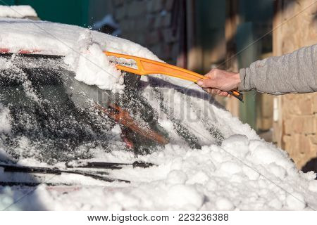scraping snow from car winter . In the park in nature