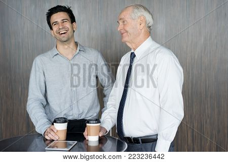 Smiling senior man in tie his young colleague drinking coffee and laughing. Executive and project manager having fun during coffee break. Business meeting and work balance concept