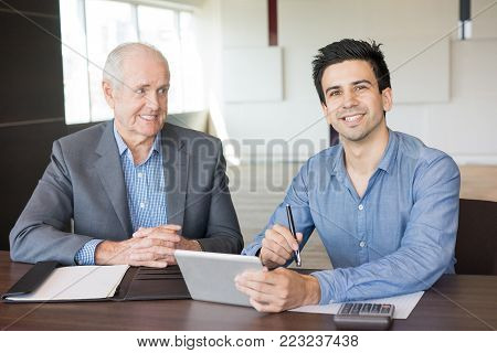 Content senior and junior coworkers using tablet in conference room. CEO and project manager estimating profit. Business meeting, success and teamwork concept
