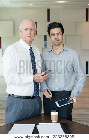Two strict business people looking at camera. Senior partner using smartphone, junior one holding tablet. Business meeting and communication concept