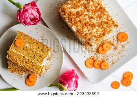 sweet carrot cake dessert slices with cream from sour cream over white wooden background, spring pink tulip flowers