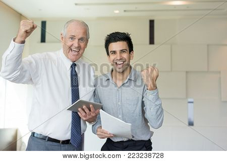 Two smiling office employees holding tablet and paper and showing winning gesture. Senior and junior colleagues closing good deal. Business meeting and success concept