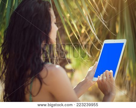 Traveler woman using tablet computer with blank blue screen in tropical beach symbolizing the ability to blend work and rest while working from anywhere. Close-up of sensual young brunette mixed race Asian Caucasian girl wearing swimsuite with wet hair su