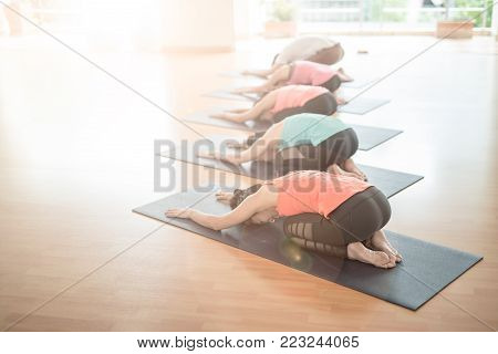 fitness, sport, training, yoga and people concept - Asian woman stretching in gym.Group Of female Doing Yoga Indoors